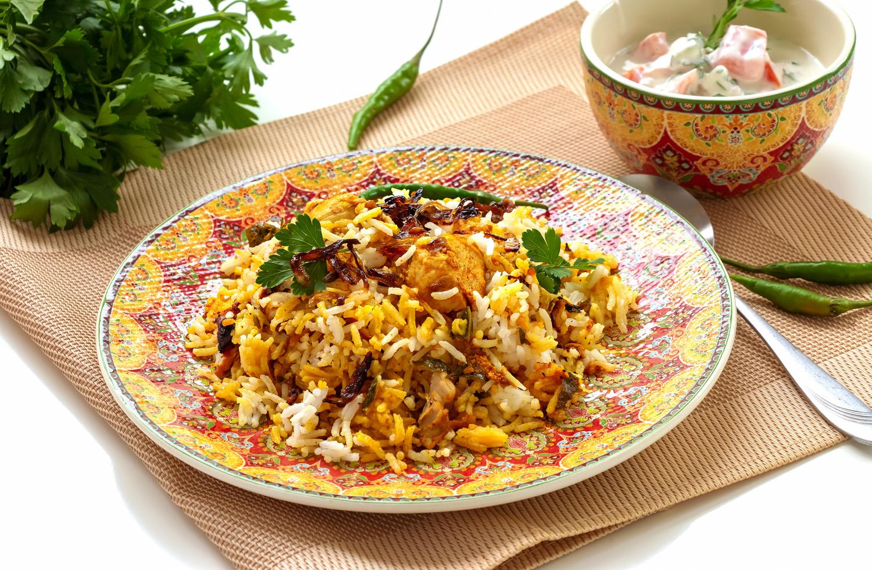 Halal Indian chicken Biryani served with yogurt tomato raita ove